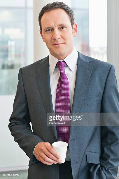 Portrait of a confident businessman holding coffee cup