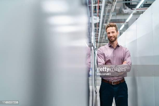 portrait of a confident businessman in a modern factory - ingenieur stock-fotos und bilder