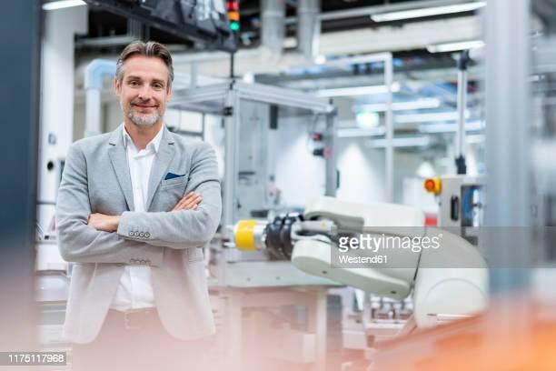 portrait of a confident businessman in a modern factory - rechnerunterstützte fertigung stock-fotos und bilder