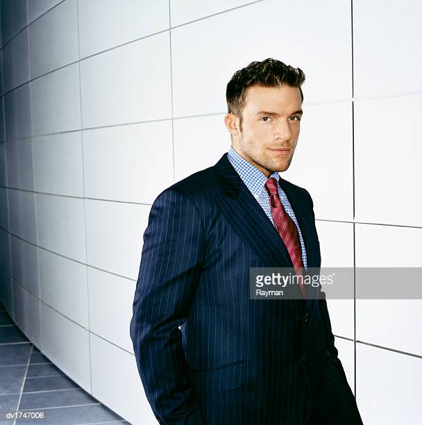 Portrait of a Confident Businessman in a Pinstripe Suit Standing By a Wall