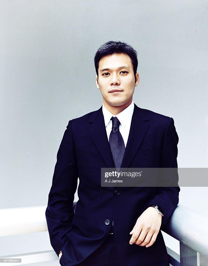 Portrait of a Confident Businessman Leaning Against a Railing : Stock Photo