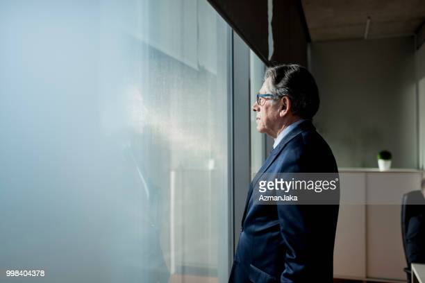 portrait of a confident businessman looking out the window - aggression stock photos and pictures