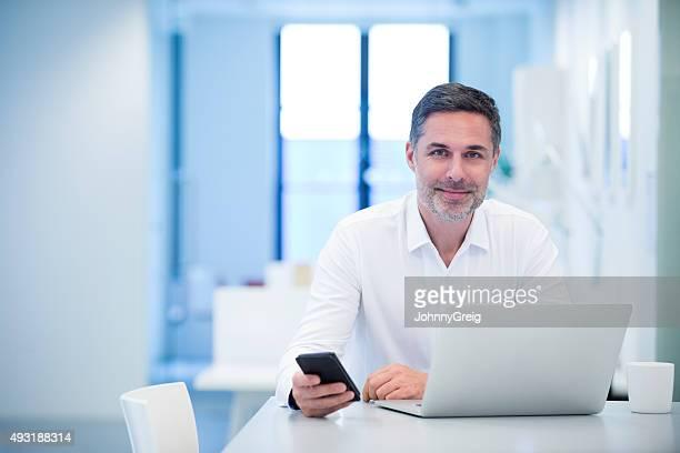 Retrato de un hombre de negocios sentado en la computadora portátil sumamente