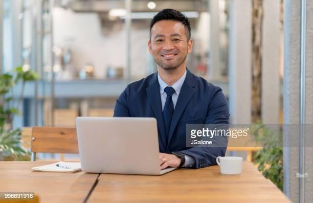 オフィスのコンピューターを使用して自信を持っているビジネスマンの肖像画