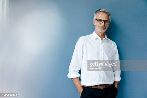 portrait of a confident businessman with hands in pockets - vêtement de peau photos et images de collection