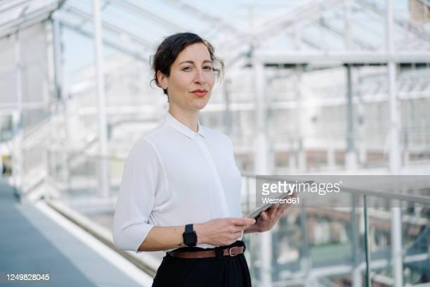 portrait of a confident businesswoman holding tablet - blouse fotografías e imágenes de stock