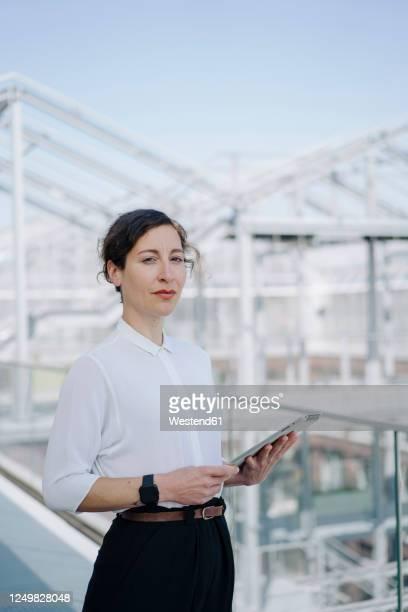 portrait of a confident businesswoman holding tablet - tre fjärdedels längd bildbanksfoton och bilder