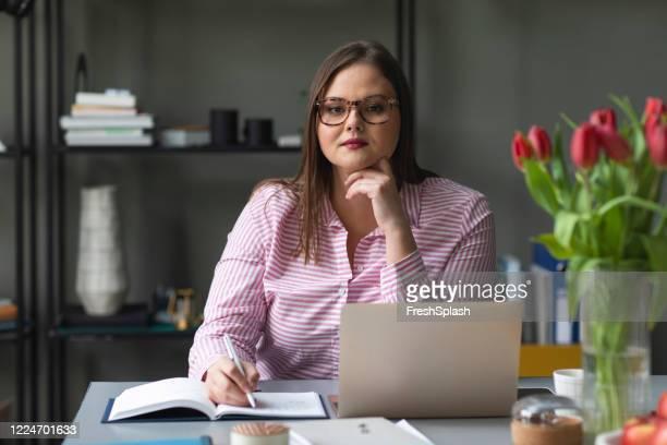 ritratto di un'imprenditrice fiduciosa seduta nel suo ufficio, guardando la macchina fotografica - big fat women foto e immagini stock