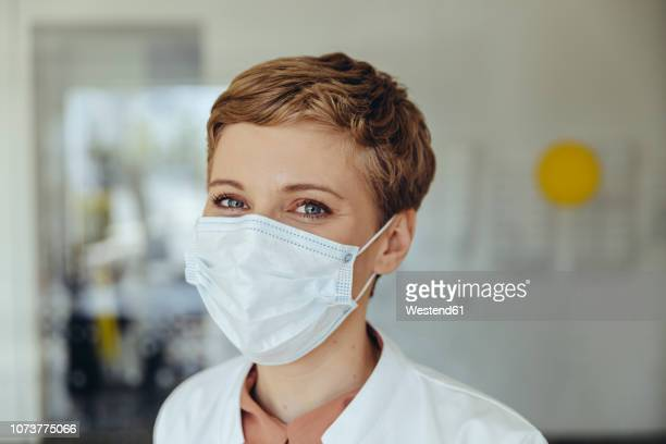 portrait of a confident female doctor, wearing surgical mask - grippeschutzmaske stock-fotos und bilder