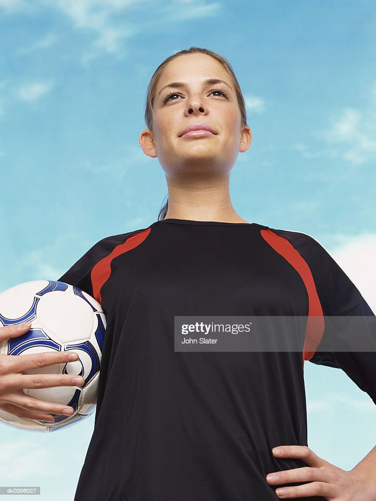 Portrait of a Confident Female Football Player Holding a Football : Stock Photo