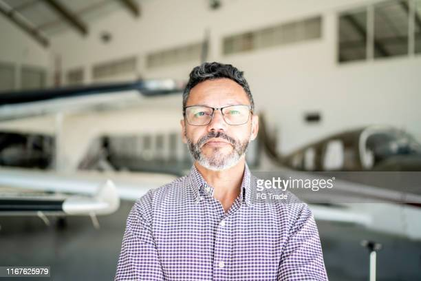 portrait of a confident man in a hangar - aerospace stock pictures, royalty-free photos & images