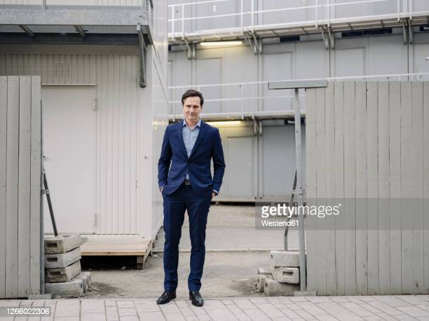 portrait of a confident mature businessman standing at a construction site - blue suit stock pictures, royalty-free photos & images