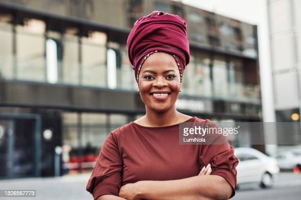 portrait of a confident mature businesswoman standing with her arms crossed in the city - headdress stock pictures, royalty-free photos & images
