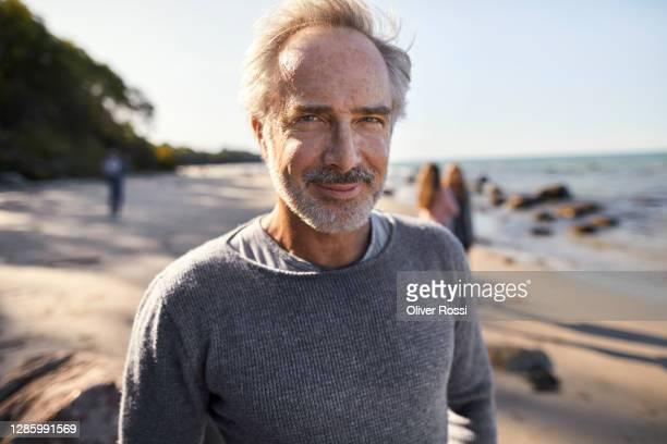 portrait of a confident mature man on the beach - quinquagénaire photos et images de collection