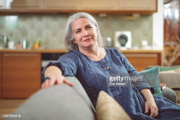portrait of a confident mature woman at home - fat old lady stock photos and pictures