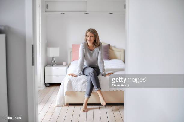 portrait of a confident mature woman sitting on bed at home - sitting stock pictures, royalty-free photos & images