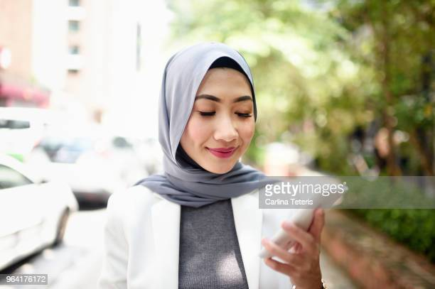 portrait of a confident muslim business woman using her phone - modest clothing stock pictures, royalty-free photos & images