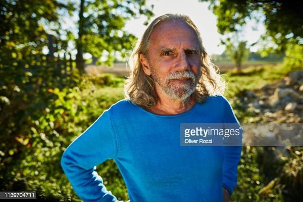 portrait of a confident seniorr man in garden - langärmlig stock-fotos und bilder