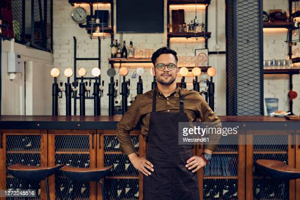 portrait of a confident waiter at the counter in a pub - bartender stock pictures, royalty-free photos & images