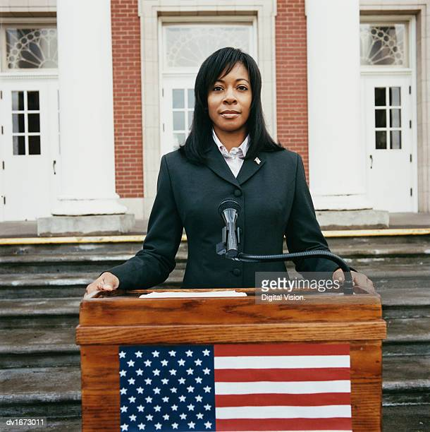 portrait of a confident woman standing at a podium - politician stock pictures, royalty-free photos & images