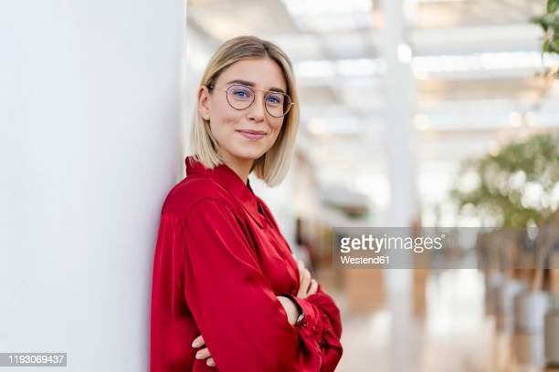 portrait of a confident young businesswoman leaning against a column - geschäftsleben stock-fotos und bilder