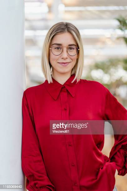 portrait of a confident young businesswoman leaning against a column - blouse stock pictures, royalty-free photos & images
