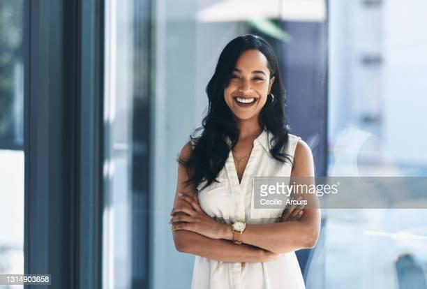 verticale d'une jeune femme d'affaires confiante restant dans un bureau - directrice photos et images de collection