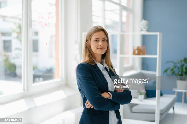 portrait of a confident young businesswoman, standing in office - oberkörperaufnahme stock-fotos und bilder