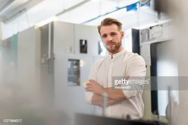portrait of a confident young man in a factory - rolled up sleeves stock pictures, royalty-free photos & images
