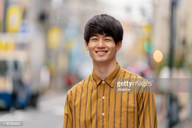 portrait of a confident young man outdoors on the street - jgalione stock pictures, royalty-free photos & images