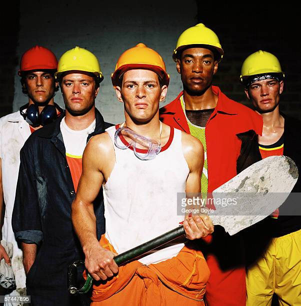 portrait of a construction worker holding a shovel with a group of men in hard hats behind him
