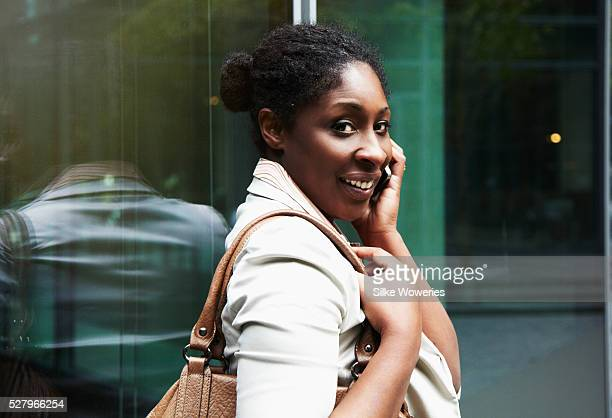 portrait of a content afro-american businesswoman taking on her smartphone - nigeria stock pictures, royalty-free photos & images