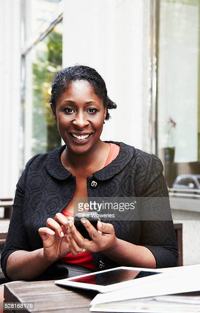 portrait of a content afro-american businesswoman typing on her smartphone - nigeria stock pictures, royalty-free photos & images