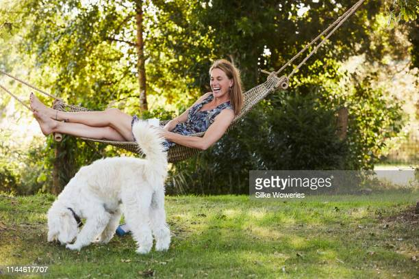 portrait of a content handsome mature woman laying in her hammock in her garden - gras stock pictures, royalty-free photos & images