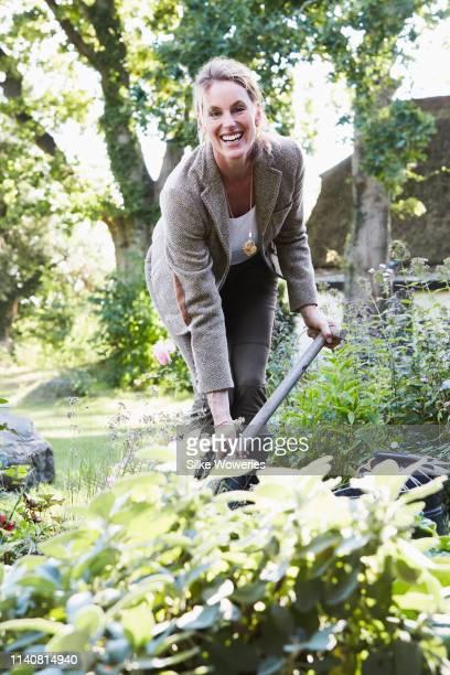 portrait of a content mature adult woman gardening - image stock-fotos und bilder