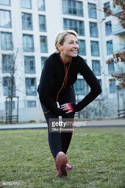portrait of a content mature woman stretching after a run in the city - 50 59 years stock pictures, royalty-free photos & images