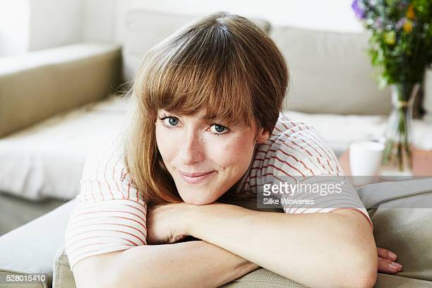 portrait of a content mid-adult woman sitting on a sofa
