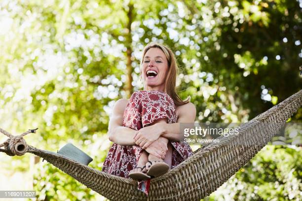portrait of a content middle aged happy woman sitting in a hammock - nature stock pictures, royalty-free photos & images