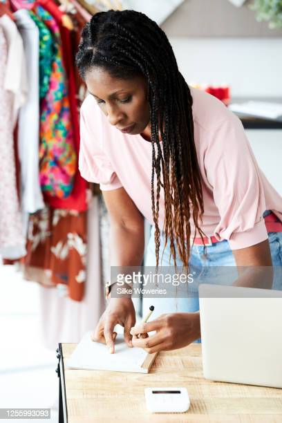 portrait of a content small business owner writing down a new order - down blouse stock-fotos und bilder