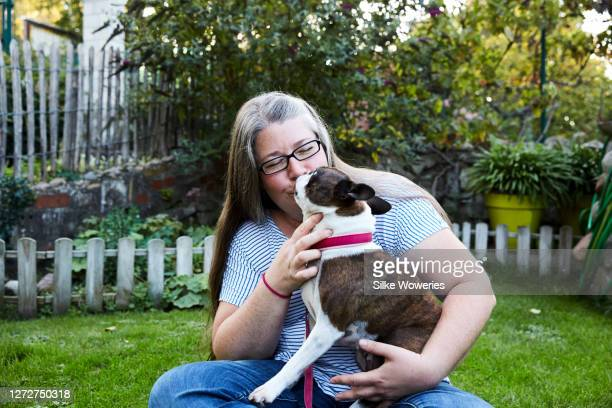 portrait of a content woman in her 50is cuddling her boston terrier dog - 1 minute 50 ストックフォトと画像