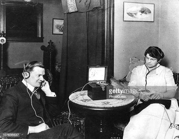 Portrait of a couple as they listen to an Aeriola Jr crystal radio set with earphones late 1910s or early 1920s