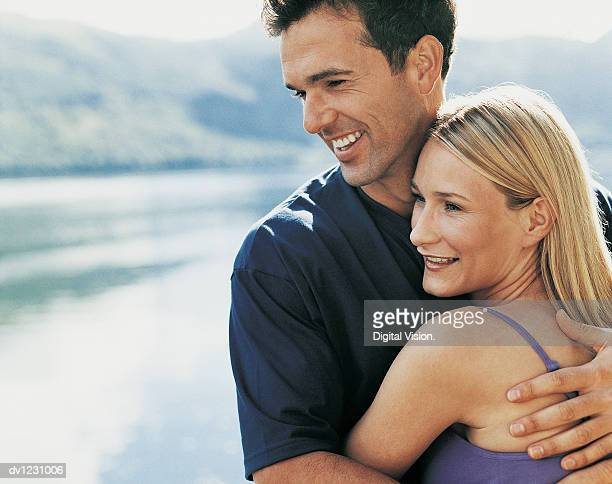 portrait of a couple embracing beside a lake - next to stock pictures, royalty-free photos & images