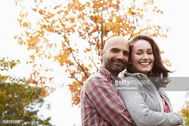 portrait of a couple embracing each other and smiling on a autumn day, backlit