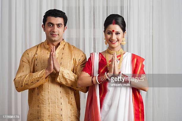 portrait of a couple greeting and smiling - prayer pose greeting bildbanksfoton och bilder