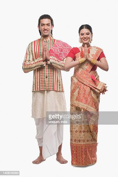 portrait of a couple greeting in traditional clothing - prayer pose greeting bildbanksfoton och bilder