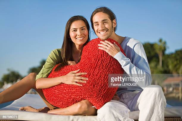 Portrait of a couple holding a heart shaped cushion