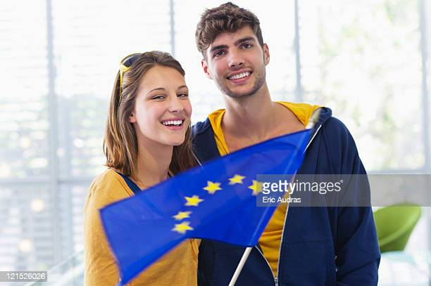 Portrait of a couple holding European union flag at an airport