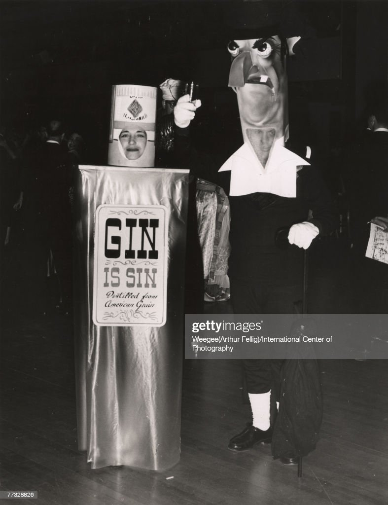 Portrait of a couple in costume at a party, 1940s or 1950s. The woman on the left is dressed as a bottle of Gin with a label that reads 'Gin is Sin, Distilled from American Grain,' the man wears an oversized head mask and lifts a glass in mock toast. (Photo by Weegee(Arthur Fellig)/International Center of Photography/Getty Images)