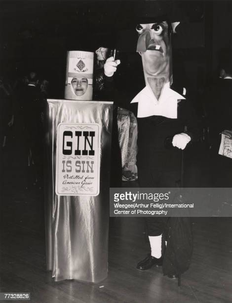 Portrait of a couple in costume at a party 1940s or 1950s The woman on the left is dressed as a bottle of Gin with a label that reads 'Gin is Sin...