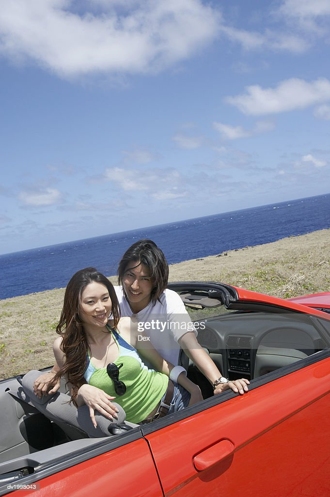 Portrait of a Couple in the Front Seat of a Convertible, by the Sea : Stock Photo